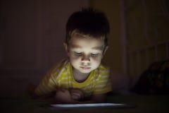 Παιδί με την ταμπλέτα στο σκοτάδι Στοκ εικόνα με δικαίωμα ελεύθερης χρήσης
