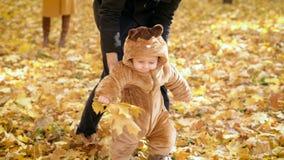 Παιδί με τη βοήθεια του πατέρα του που πηδά στα φυλλάδια στο δάσος απόθεμα βίντεο
