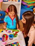 Παιδί με τη ζωγραφική μητέρων στον πίνακα εγγράφου στο σπίτι Στοκ Εικόνες