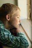 Παιδί με τη λυπημένη συνεδρίαση έκφρασης κοντά στο παράθυρο στοκ εικόνες