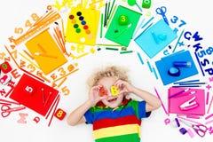 Παιδί με τις προμήθειες σχολείων και σχεδίων Σπουδαστής με το βιβλίο στοκ εικόνες