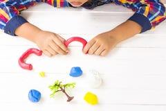 Παιδί με τον άργιλο και τη χρησιμοποίηση της δημιουργικότητας για την παραγωγή της κόκκινης πόρτας του κήπου και κ.λπ. Τοπ άποψη  Στοκ Φωτογραφίες
