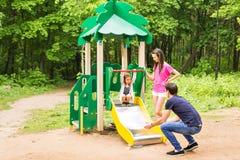 Παιδί με τους γονείς στην παιδική χαρά Mom, μπαμπάς και κόρη οικογενειακό παιχνίδι Στοκ εικόνες με δικαίωμα ελεύθερης χρήσης