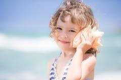 Παιδί με το θαλασσινό κοχύλι στοκ φωτογραφία