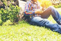 Παιδί με το κινητό τηλέφωνο στο χέρι του, ή παιδί Ασιάτης που χαμογελά και ευχαριστημένος από το κινητό τηλέφωνο στον κήπο Ζουμ μ Στοκ φωτογραφία με δικαίωμα ελεύθερης χρήσης