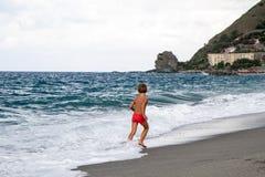 Παιδί με το πορτοκαλί μαγιό που τρέχει στην παραλία Στοκ Εικόνα
