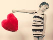 Παιδί μικρών κοριτσιών με το κόκκινο μαξιλάρι μορφής καρδιών Στοκ Εικόνα