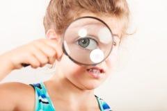 Παιδί μικρών κοριτσιών που κοιτάζει μέσω της ενίσχυσης - γυαλί Στοκ εικόνα με δικαίωμα ελεύθερης χρήσης