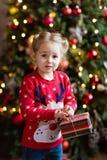 Παιδί μικρών κοριτσιών στο κόκκινο πουλόβερ που κρατά ένα δώρο στο νέο BA έτους Στοκ Εικόνες