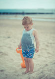 Παιδί μικρών παιδιών που στέκεται με ένα υγρό πουκάμισο στην παραλία στοκ εικόνες