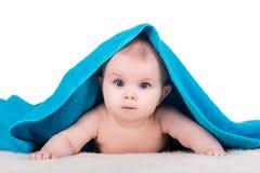 Παιδί μωρών με τα μεγάλα μάτια κάτω από την μπλε πετσέτα Στοκ εικόνα με δικαίωμα ελεύθερης χρήσης