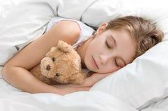 Παιδί που αγκαλιάζει τη teddy αρκούδα της στον ύπνο Στοκ Φωτογραφία