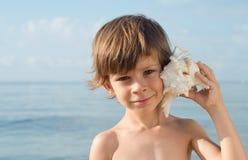 Παιδί που ακούει conch Στοκ Φωτογραφία