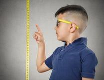 Παιδί που δείχνει στο ύψος του στη μέτρηση της ταινίας στοκ εικόνα με δικαίωμα ελεύθερης χρήσης