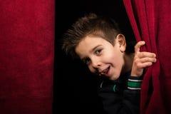 Παιδί που εμφανίζεται κάτω από την κουρτίνα στοκ εικόνες