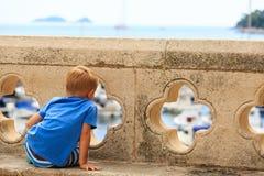 Παιδί που εξετάζει Dubrovnik από τους παλαιούς τοίχους πόλεων Στοκ Φωτογραφίες