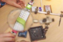 Παιδί που εργάζεται με το γυαλί πιό magnifier Στοκ Φωτογραφίες
