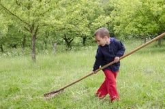 Παιδί που εργάζεται σε έναν κήπο με την τσουγκράνα Στοκ φωτογραφία με δικαίωμα ελεύθερης χρήσης
