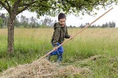 Παιδί που εργάζεται σε έναν κήπο με την τσουγκράνα Στοκ Φωτογραφία