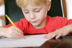 Παιδί που εστιάζει στην εργασία όπως γράφει με το μολύβι Στοκ Εικόνες