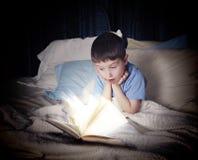 Παιδί που διαβάζει το ανοικτό βιβλίο τη νύχτα στο κρεβάτι Στοκ Φωτογραφίες
