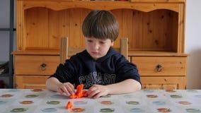 Παιδί που διαμορφώνει τον πορτοκαλή άργιλο φιλμ μικρού μήκους