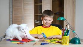 Παιδί που κάνει τις διακοσμήσεις Χριστουγέννων με τη γάτα στον πίνακα Κάνετε τη διακόσμηση Χριστουγέννων με τα χέρια σας Στοκ φωτογραφία με δικαίωμα ελεύθερης χρήσης