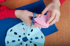 Παιδί που κάνει snowflakes εγγράφου Στοκ φωτογραφία με δικαίωμα ελεύθερης χρήσης