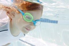 Παιδί που κολυμπά στη λίμνη υποβρύχια στοκ εικόνες