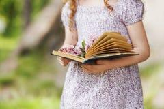 Παιδί που κρατά το ανοικτό βιβλίο και μια ανθοδέσμη της πασχαλιάς στοκ φωτογραφία