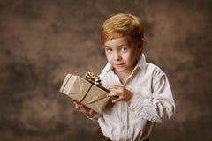 Παιδί που κρατά το παρόν κιβώτιο δώρων, εκλεκτής ποιότητας ύφος. στοκ εικόνες
