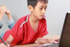 Παιδί που μελετά με τα βιβλία και το lap-top Στοκ Εικόνες
