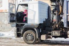Παιδί που οδηγεί ένα φορτηγό Παιδικά παιχνίδια στο οδηγό φορτηγού το παιδί γυρίζει τη ρόδα ενός μεγάλου φορτηγού στοκ φωτογραφία με δικαίωμα ελεύθερης χρήσης