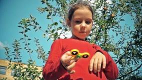 Παιδί που παίζει το δημοφιλές fidget παιχνίδι κλωστών φιλμ μικρού μήκους