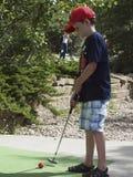 Παιδί που παίζει το μικροσκοπικό γκολφ Στοκ Εικόνες