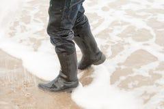 Παιδί που περπατά στη θάλασσα με τις μπότες Στοκ Εικόνες
