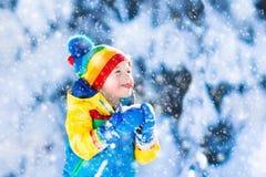 Παιδί που πιάνει το χιόνι στο χειμερινό πάρκο Στοκ Φωτογραφία
