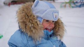 Παιδί που στέκεται και γλυκός που χαμογελά στο χειμώνα απόθεμα βίντεο