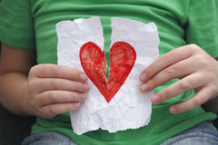 Παιδί που σχίζει την κόκκινη καρδιά σε ένα κομμάτι χαρτί στοκ φωτογραφίες