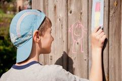 Παιδί που σύρει μια εικόνα κιμωλίας Στοκ φωτογραφία με δικαίωμα ελεύθερης χρήσης