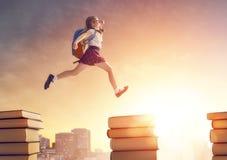 Παιδί που τρέχει και που πηδά στα βιβλία Στοκ Φωτογραφίες