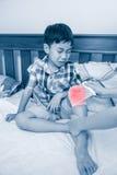 Παιδί που τραυματίζεται Μητέρα που επιδένει το γόνατο γιων ` s Στοκ Φωτογραφία