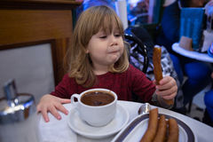 Παιδί που τρώει τα μπαστούνια με το chocolat Στοκ Φωτογραφίες