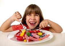 Παιδί που τρώει την καραμέλα όπως τρελλό στην κατάχρηση ζάχαρης και την ανθυγειινή γλυκιά έννοια διατροφής Στοκ Φωτογραφίες