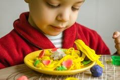 Παιδί που φαίνεται το πιάτο μακαρονιών του, που γίνεται με το plasticine Στοκ εικόνα με δικαίωμα ελεύθερης χρήσης
