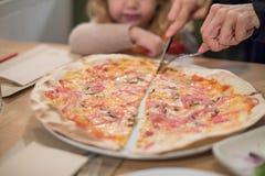Παιδί που φαίνεται χέρια μητέρων που διαιρούν σε μισή πίτσα Στοκ φωτογραφία με δικαίωμα ελεύθερης χρήσης