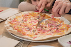 Παιδί που φαίνεται χέρια μητέρων που κόβουν την πίτσα με το δίκρανο και το μαχαίρι Στοκ φωτογραφία με δικαίωμα ελεύθερης χρήσης