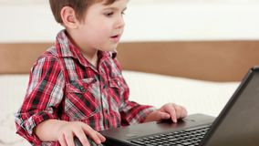 Παιδί που χρησιμοποιεί το lap-top, τα παίζοντας παιχνίδια στον υπολογιστή μικρών παιδιών που χρησιμοποιούν touchpad και το ασύρμα απόθεμα βίντεο