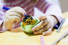 Παιδί που χρωματίζει ένα αυγό Στοκ φωτογραφία με δικαίωμα ελεύθερης χρήσης