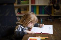 Παιδί που χρωματίζει το άσπρο φύλλο στον ξύλινο πίνακα Στοκ φωτογραφίες με δικαίωμα ελεύθερης χρήσης